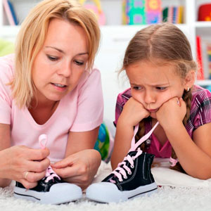 ребенок учится завязывать шнурки
