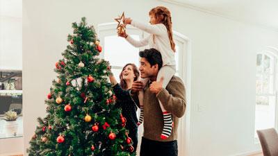 семья наряжает елку и создает новогоднее настроение в квартире