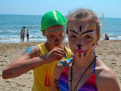 дети на пляже разрисовывают друг друга